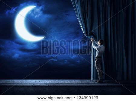 Businessman stands on the scene with curtains over night city background