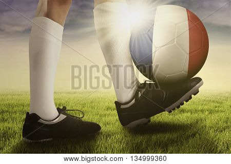 Soccer ball with national flag of France on the foot of a football player shot on the meadow