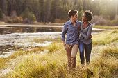 Mixed race couple embracing, walking near a rural lake poster