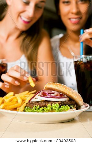 Fast food hamburger and fries in a restaurant on a dish - close-up and focus on the burger