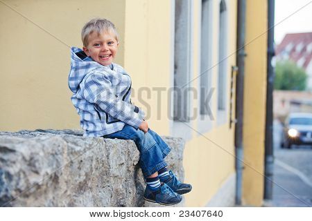 little boy sits near the old house