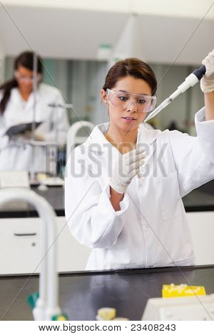 Portrait of a student pouring a liquid in a tube in a laboratory