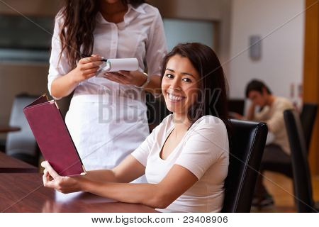 Smiling woman ordering a meal in a restaurant