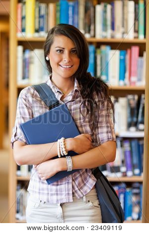 Portrait of a cute student posing with a book in the library