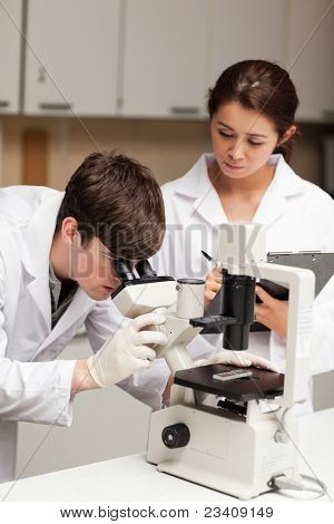Portrait of a scientist looking in a microscope while his colleague is taking notes in a laboratory