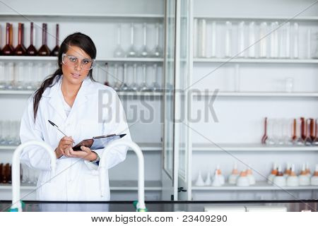 Cute female scientist writing on a clipboard while looking at the camera