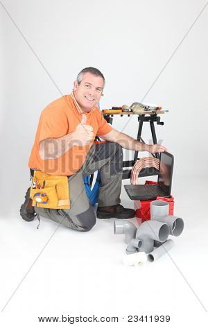 Man kneeling with laptop computer and plumbing tools