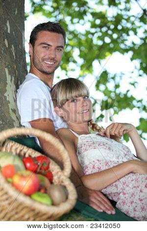 Couple sat by tree with basket of fresh produce