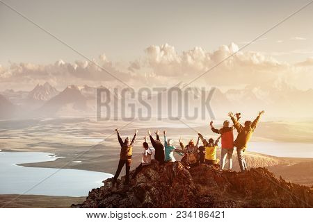 poster of Big Group Of People Having Fun In Success Pose With Raised Arms On Mountain Top Against Sunset Lakes