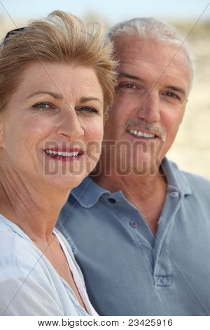 Middle-aged couple stood on beach