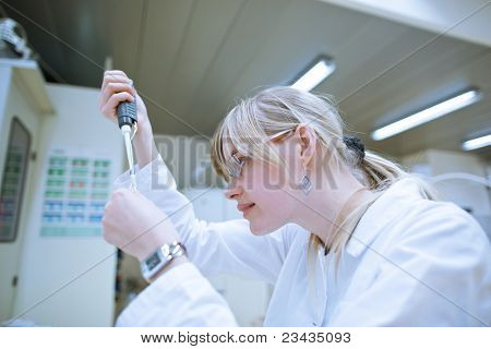 Closeup of a female researcher/chemistry student carrying out research experiments in a chemistry lab (color toned image)