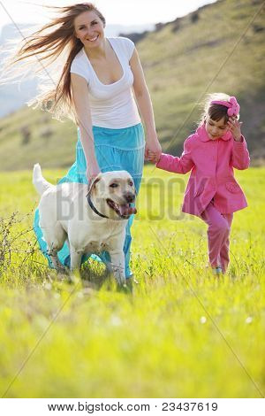Happy family walking with dog in green field