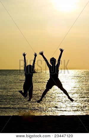 Couple Jumping In Silhouette
