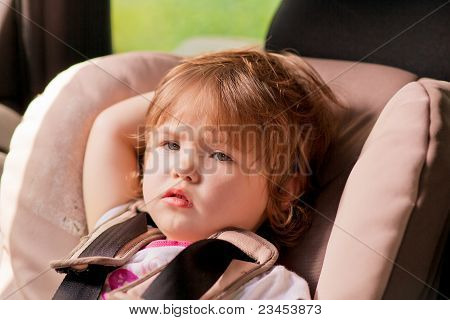 Portrait Of Unhappy Litle Kid In Safety Seat