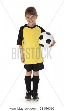 Full length view of seven year old girl holding soccer ball on white background