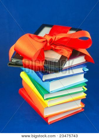 Electronic Book Reader Tied Up With Red Ribbon On The Stack Of Books