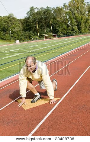 Middle Age Senior Man Exercising Running On Sports Field And Running Track