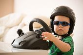 Cute Little Kid Boy In A Helmet Playing With Computer Steering Wheel. Future Driver. Getting Ready F poster