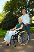 Nurse Driving Senior Woman In Wheelchair