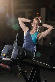 Woman Doing Strength Exercises For Abdominal Muscles At Indoor Sport Gym. Girl Doing Yoga Stretches  poster