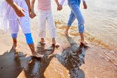 Barefoot girls walking down sandy beach along coastline in warm water on summer day poster
