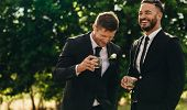 Groom And Best Man Drinking And Smiling During Wedding Party. Groom And Groomsmen Partying After Wed poster