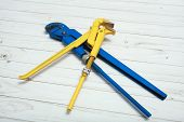Two Adjustable Pipe Wrench In Blue And Yellow, Pliers, Wrenches Or Plumbing Tool, On A White Wooden  poster