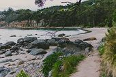 Deserted Beach In Hobart, Tasmania With Rocks And Walkpath In The Foreground On An Overcast Day With poster