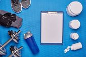 Sports  nutrition (supplements), sneakers, dumbbells and sports accessories on a blue background. To poster