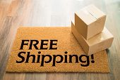 Free Shipping Welcome Mat On Wood Floor With Shipment of Boxes. poster