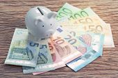 White Piggy Bank On Pile Of Euro Banknotes On Wooden Table, Financial Savings Money Account Or Europ poster