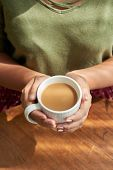 Close-up Shot Of Female Hands Holding Cup Of Delicious Cappuccino, Table Surface Illuminated With Su poster