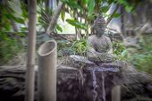 Peaceful And Spiritual Grey Stone Buddha Searching For Enlightenment With Mini Waterfall, Natural Pl poster