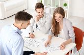 Real estate agent showing plan of apartment to clients in office poster