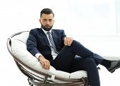 confident businessman sitting in a chair poster