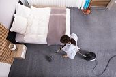 Happy Young Housekeeper Cleaning Carpet With Vacuum Cleaner In Hotel Room poster