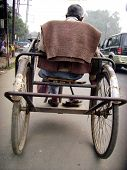 picture of physically handicapped  - A physically handicapped indian man proudly going to work in Lucknow India on his hand driven tricycle - JPG