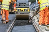 Steamroller Workers Construct Asphalt Road And Railroad Lines poster