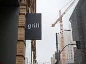 Grill Sign Displayed Outside Of Restaurant On A Foggy, Overcast Day poster