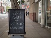 Keep Calm And Get Your Nails Done Street Sign On Display On A Sidewalk poster