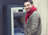 Handsome Confident Man In Outwear Inserting Plastic Card Into Atm Machine And Smiling At Camera. poster