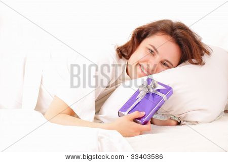 Pretty Young Woman Relaxing In Bed With A Gift