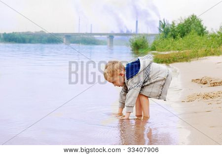 Little Boy On The River Coast Near Industrial Plant