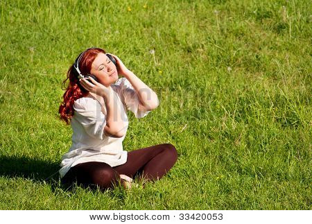 Beautiful Redhead Young Woman Listening To Music With Headphones On Grass Lawn