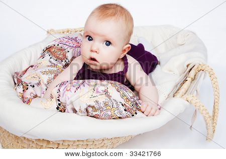 The Little Girl Is A Baby In A Basket On A Beautiful Fabric And White Plaid, And Drooling.