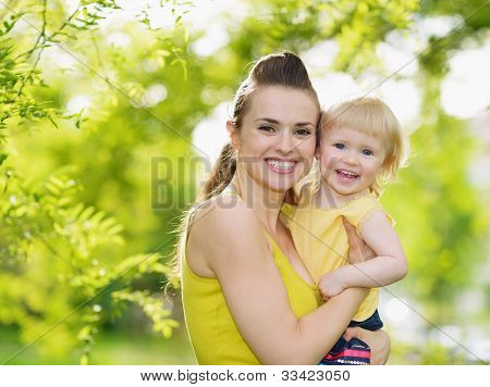 Portrait Of Smiling Mother And Baby Girl Outdoors