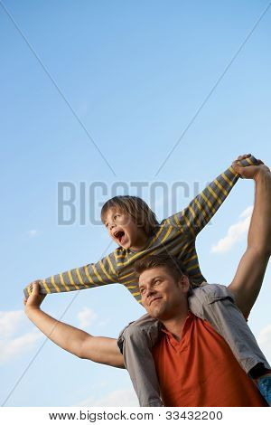 Happy Son On The Shoulders Of The Father