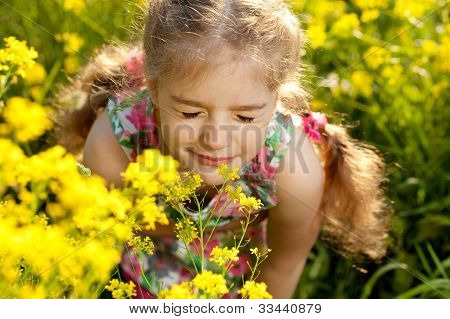Little Blonde Girl Inhales Scent Of Flowers