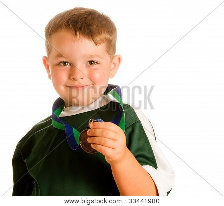 Happy child in soccer or football uniform with medal isolated on white