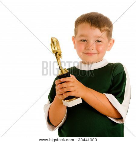 Happy child in soccer or football uniform with trophy isolated on white